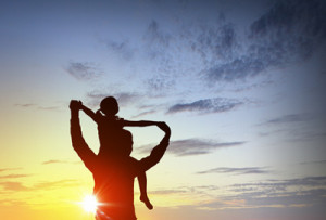 Father and little daughter silhouettes on sunset background